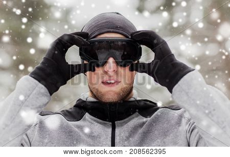fitness, winter sport, people and healthy lifestyle concept - young man in ski goggles outdoors