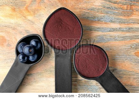 Spoons with acai powder and berries on wooden background