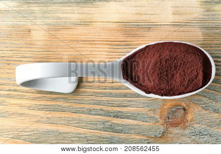 Spoon with acai powder on wooden background