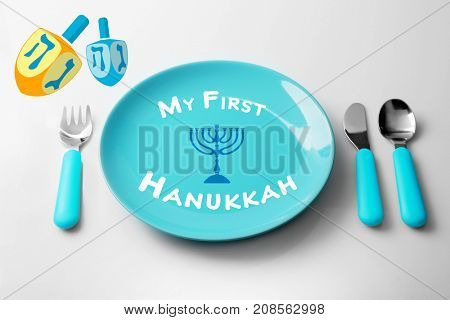 Plate with text MY FIRST HANUKKAH and cutlery on light background