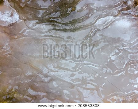 Texture of thick frozen sheet of ice forming on surface of flowing cold river water during winter time
