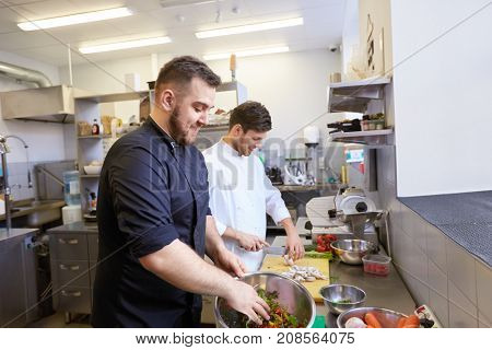 cooking food, profession and people concept - happy male chef and cook with knife chopping champignons and making salad at restaurant kitchen