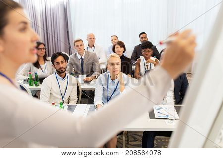 business and education concept - businesswoman or lecturer writing to whiteboard for group of people at conference, presentation or lecture
