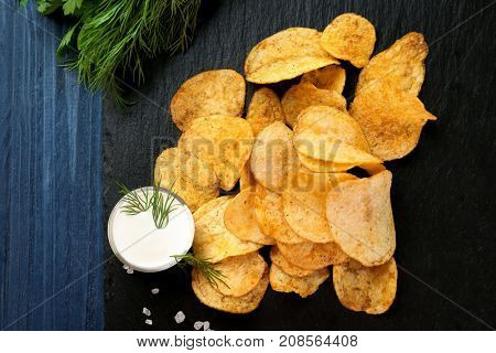 Potato chips and sour cream in bowl on slate plate