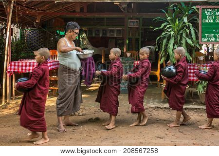Bagan, Myanmar - October 13, 2016: Young buddhist novices walk to collect alms and offerings on the streets of Bagan, Myanmar.