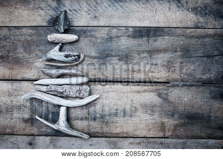 Christmas tree made of driftwood on a wooden background