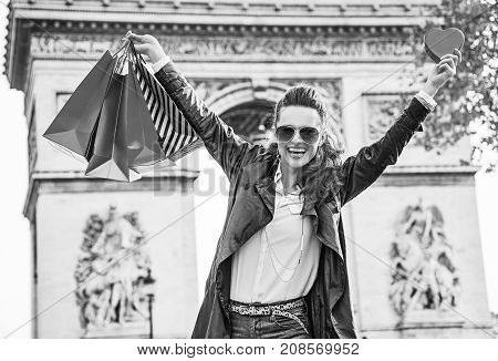 Stylish Valentine's Day in Paris. smiling elegant fashion-monger in sunglasses with shopping bags in Paris France showing red heart shaped box of chocolates and rejoicing