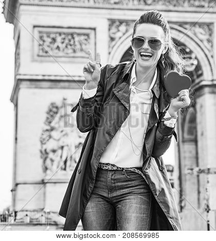 Stylish Valentine's Day in Paris. Portrait of happy young fashion-monger in trench coat in Paris France showing red heart shaped box of chocolates