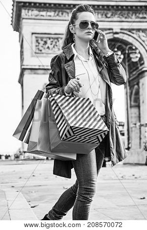 Stylish autumn in Paris. trendy woman in trench coat with shopping bags near Arc de Triomphe in Paris France using a cell phone