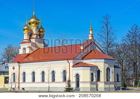 SAINT-PETERSBURG, RUSSIA, april 01: A small Orthodox church with golden domes and a red roof against the blue sky on a bright Sunny day of 01 april 2017.