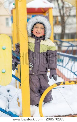 Portrait smiling happy little baby boy plays with a snow outdoor. Winter day. Happy family. Positive human emotions feelings joy. Active winter game.