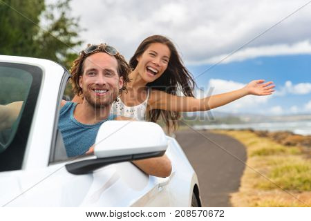 Car road trip couple summer fun on travel vacation freedom. Happy free people in convertible cabriolet driving. Asian woman carefree with open arms cheering joyful. Friends going on holidays.
