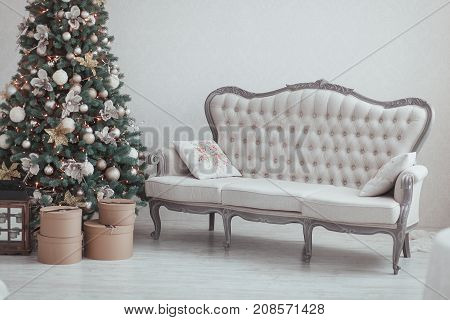 Christmas and New Year Eve Tree. Holiday winter background. Interior details - sofa in front, vintage gifts, candles. Isolated white wall.