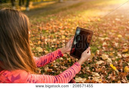 Pretty young girl using tablet outdoor lying on leaves and smiling. Woman using digital tablet pc in the autumn park. Student using tablet after school.