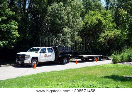 JOLIET, ILLINOIS / UNITED STATES - JULY 25, 2017: A truck and flatbed trailer, belonging to Acres Group Professional Landscape Services, is parked in the driveway of the Route 66 Park.