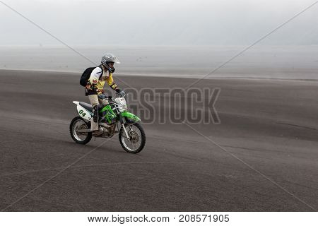 Java, Indonesia - Apr 19, 2015: Tourist Riding Offroad Bike Through Black Ash Sand Dunes In Bromo Te