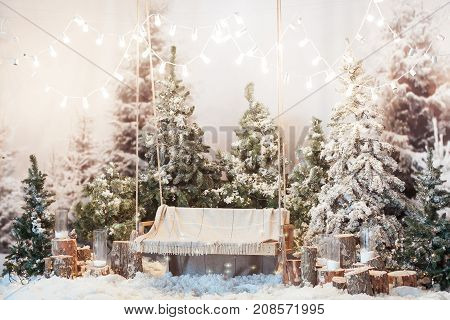 Wooden swing in a snow-covered park or forest with spruce trees and stumps, big candles in glass vases, while snowing, Christmas and New Year holiday indoor concept.