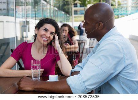 Joyful laughing caucasian woman flirting with african american man at restaurant