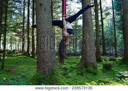 Women is doing acrobatics in the forest, showing an aerial split upside down.