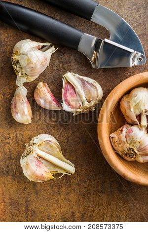 Fresh garlic and garlic presser on kitchen table. Top view.