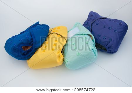 Variety of blue yellow violet baby reusable diapers panties lay on white background