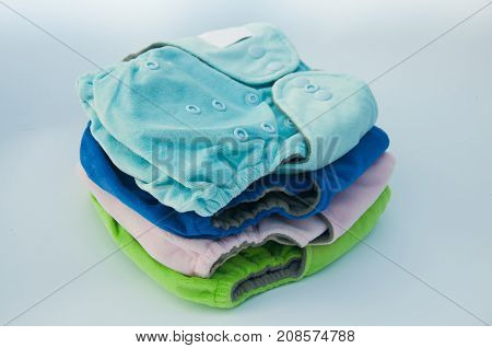 Heap of blue green pin cotton baby reusable diapers with buttons laying on white background