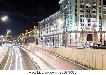 Triumph Square and transport metropolis traffic and blurry lights of cars on multi-lane highways and road junction at night in Moscow