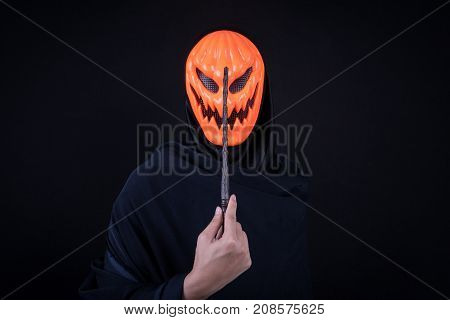 Mystery man with orange pumpkin evil mask holding magic wand on black background Halloween night costume concept