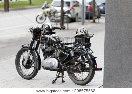 STOCKHOLM SWEDEN - SEPT 02 2017: TBeautiful black old retro motorcycle and helmet on the tank at the Mods vs Rockers event at the Saint Eriks bridge Stockholm Sweden September 02 2017