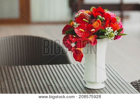 A bouquet of different red flowers in a white vase on a table. Close-up. Artwork. Copy space