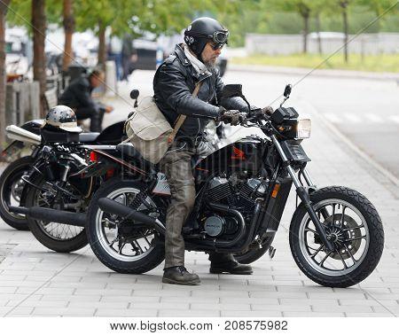 STOCKHOLM SWEDEN - SEPT 02 2017: TTough senior motorcyclist wearing leather jacket and beard at the Saint Eriks bridge Stockholm Sweden September 02 2017