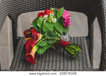 Wedding bouquet with bright red flowers and ribbon with a silver brooch on the stalk. Close-up. Artwork. Copy space
