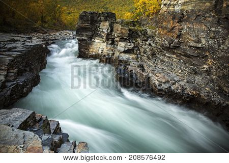 Soft rapids in a river, surrounded of cliffs, rocks. Some sunshine. Colorful forest in the background.