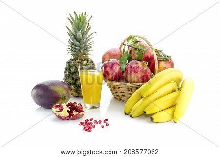 Mango, pineapple, bananas, garnet and fruit juice on white background closeup