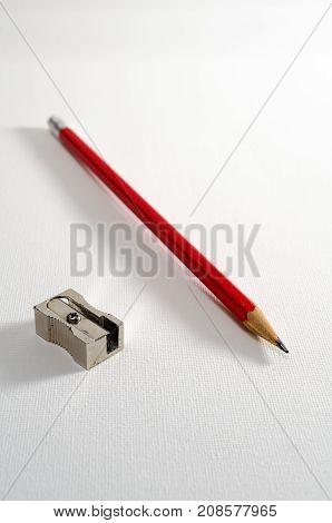 A Studio Photograph of a Pencil and a Metal Pencil Sharpener