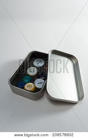 A Studio Photograph of a Metal Tin Containing Assorted Buttons
