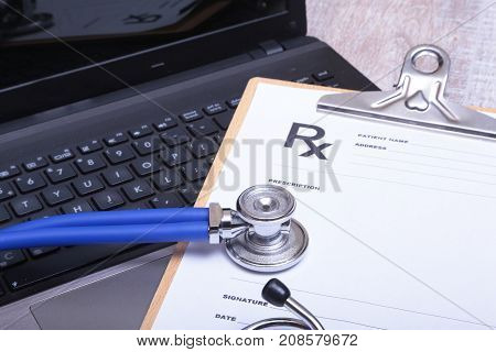 Prescription form with laptop computer and medical stethoscope.