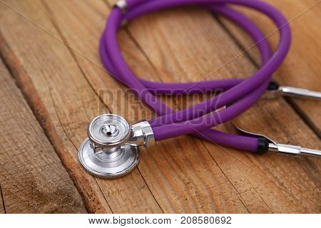 Closeup of a medical stethoscope isolated on wooden background.