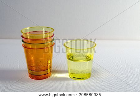 A Studio Photograph of Multicoloured Plastic 'Shot' Containers with One Full Container and a Number of Empties