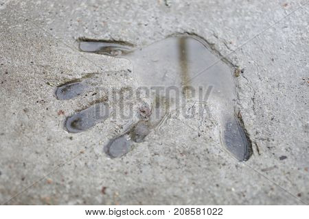 Human hand print on grey concrete slab with water at rainy day