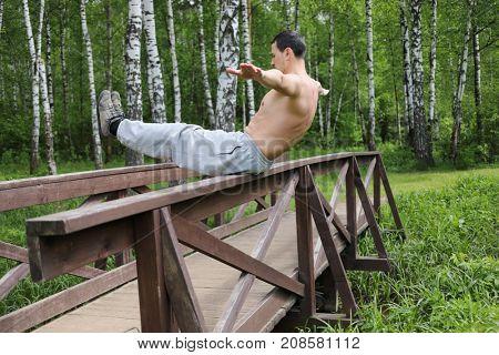 Athlete man balances on railing of wooden bridge in summer forest
