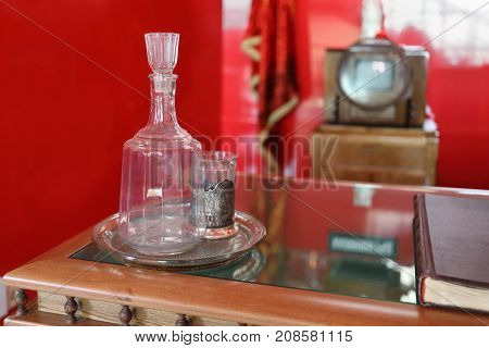 Soviet glass decanter, glass with holder, book on table in red room