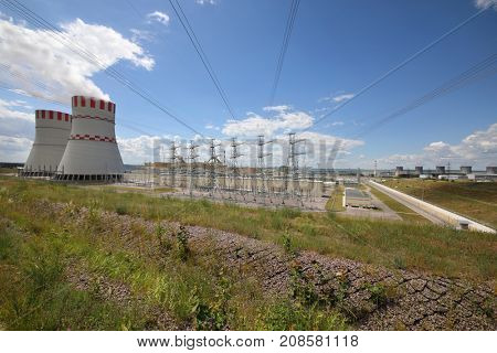 Smoking pipes, poles with wires of atomic thermal power plant at sunny day