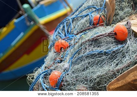 Fishing net with a colorful boat behind
