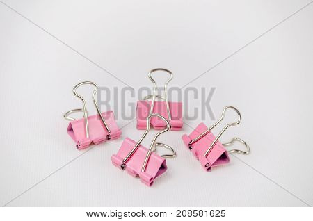 A Studio Photograph of a Group of Pink Bulldog Clips