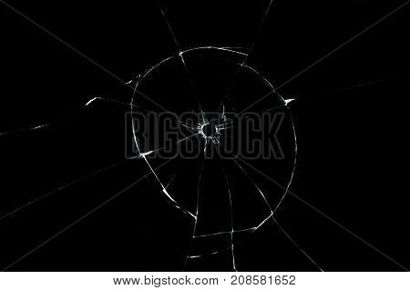 bullet hole in glass closeup on black background