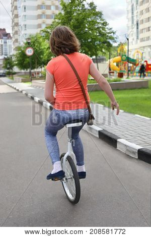 Woman rides monocycle in yard of residential buidlings at summer, back view