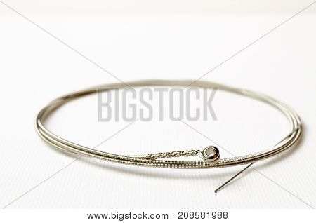 A Studio Photograph of a Wound Steel Guitar String