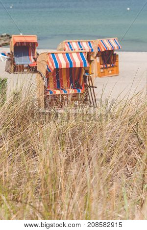 Colorfuled striped roofed chairs on sandy beach in Travemunde., Lubeck, Germany.