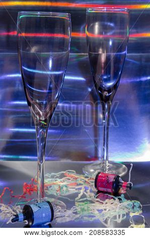 A Studio Photograph of Two Champagne Flutes and Party Poppers Set Against a Silver Holographic Backdrop